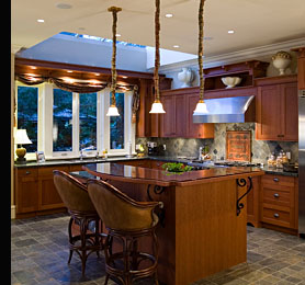 A kitchen featuring low voltage halogen down lights and pendant task lighting over the island breakfast bar