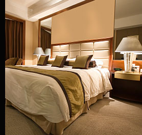 Bedroom Lighting with recessed low voltage halogen spot lights in the ceiling and large decorative bedside lamps
